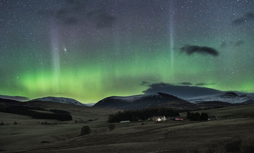 Shimmering night sky in waves of green and gold, above hills in the Scottish Highlands. With lights twinkling from a white farmstead at the foot of the hills.